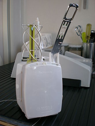Radiosonde - A GPS sonde, approx 220 × 80 ×75 mm (8.7 × 3.1 × 3 in) (with grounding station in background, used to perform a 'ground check' and also recondition the humidity sensor)