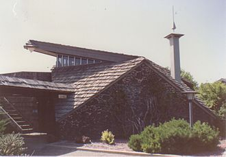 """Glen Mitchell House - Exterior image showing tower and """"swooping"""" roof"""