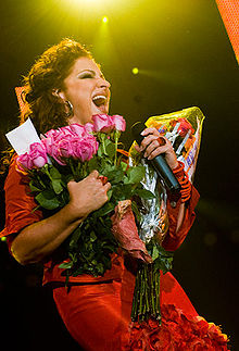 A woman stands under a spotlight. She holds several bouquets of flowers and a microphone.
