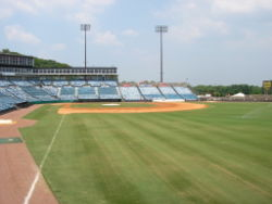 A view from right field shows the green grass and infield dirt of a baseball diamond surrounded by empty blue seats