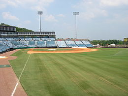 A view from the right field line of the seating bowl at Greer. Blue seats stretch from the right field wall, behind home plate, and beyond the third base dugout.