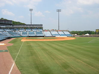 Herschel Greer Stadium - A view from right field shows the green grass and infield dirt of a baseball diamond surrounded by empty blue seats