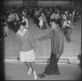 """Heart Mountain Relocation Center - """"Tubbie"""" Kunimatsu and Laverne Kurahara demonstrate some intricate jitterbug steps, during a school dance held in the high school gymnasium, November 1943."""