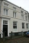 foto van Huis met gebosseerd grijsgepleisterde lijstgevel en met witte deuromlijsting