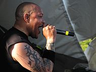 A man, with a large tattoo on his right arm, sings into a microphone while looking at the audience.