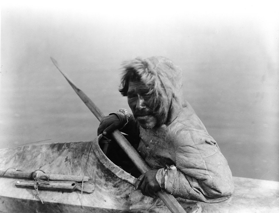 Photograph of an Inuit man seated in a kayak, holding a paddle