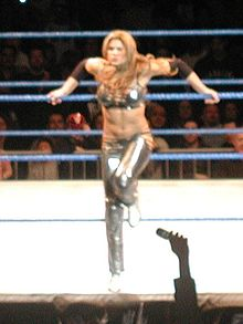 Jackie posing at the ring ropes during a WWE house show in 2005