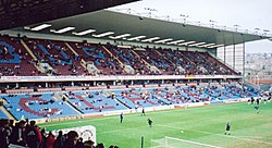 "A two-tiered cantilever football stand. The lower tier has light blue seats with some claret seats which spell the word ""Clarets"". The upper has all claret seating. Some floodlights are attached to the roof of the stand. A scattering of spectators can be seen in the seats."