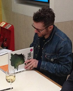 "Jamie Hewlett in 2014 signing copies of ""The Cream of Tank Girl"" at a Tank Girl lecture at the British Library- 2014-07-03 08-13.jpg"