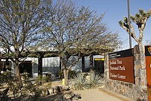 This image shows the entrance to the Joshua Tree National Park Visitor Center in Joshua Tree, California. It shows a large brown sign with the visitor center's name, as well as an outdoor sitting area with desert vegetation, such as agave plants and one Joshua Tree plant.