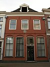Huis met lijstgevel met gepleisterde pui, gevelsteen en dakkapel