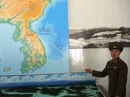 A Korean People's Army soldier pointing to the Korean Demilitarized Zone (DMZ) Korean People's Army soldier pointing to the DMZ.jpg