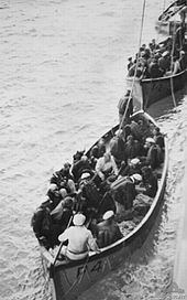 Photograph looking down on two lifeboats crammed with people in naval uniforms. A third lifeboat of a different design can be seen behind the first two.
