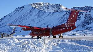 """Kulusuk Airport - Air Greenland """"Papikkaaq"""" on the tarmac under the Qalorujoorneq mountain"""