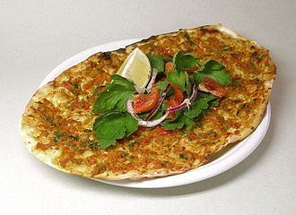 Iraqi cuisine - Lahm b'ajeen, garnished with parsley, tomato, red onion, and a wedge of lemon