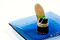 Lakserulle med spinat. Geleret laks omviklet med japansk nori-tang og en kerne af frisk kogt spinat. Pyntet med sort kaviar, rodlog, korvel og en lille skive handlavet knaekbrod med kommensmag.Tillagat av Kim Palhus, Ny Nordisk Mat (2).jpg