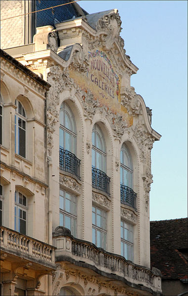 """""""Moulins possède quelques exemples de l'architecture commerciale et des décors du début du XXème siècle.L'immeuble des nouvelles Galeries se distingue par la riche ornementation de sa façade, mêlant un décor floral et végétal sculpté aux guirlandes de fleurs, et une mosaïque qui se décline en teintes douces.  La mosaïque dorée souligne l'enseigne. Les façades largement ouvertes mettent en évidence la vocation commerciale et festive du magasin.""""  Source: Le Patrimoine des Communes de l'Allier, tome II, 1999.  Léon et Marcel LAMAIZIERE (1855-1940 et 1879-1922) ont construit en France tous les magasins de cette enseigne."""