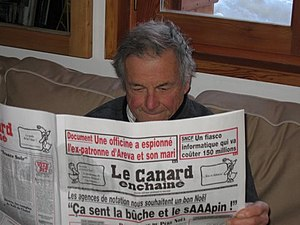 Le Canard enchaîné - A person reading the newspaper Le Canard enchaîné.