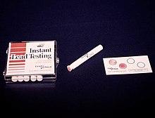 Коробка сигарет, как белые цилиндры слева, в середине белый цилиндр с розовым наконечником, справа бумага с четырьмя кругами, две заготовки и два розовый