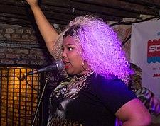 Una mujer de cabello rubio con el brazo derecho levantado y el izquierdo apoyado en la cadera canta en un micrófono en una habitación de ladrillos oscuros.