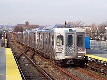 Un tren subterráneo plateado saliendo de una estación.