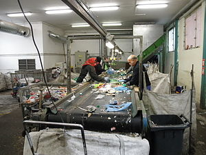 Polyethylene terephthalate - Workers sort an incoming stream of various plastics, mixed with some pieces of un-recyclable litter.