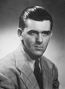 Portrait-photo en noir et blanc de Maurice Richard en costume avec une cravate