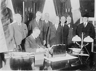 United States Tax Court - President Calvin Coolidge signing the income tax bill which established the U.S. Board of Tax Appeals; Andrew Mellon is the third figure from the right.