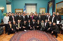 Color image ofLos 33 miners posing with the President and First Lady of Chile in the Blue Room of the Presidential Palace on 24 October 2010