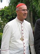 Tarcisio Kardinaal Bertone in jurk voor hete tropische landen (witte soutane met scharlakenrode biezen en knopen).