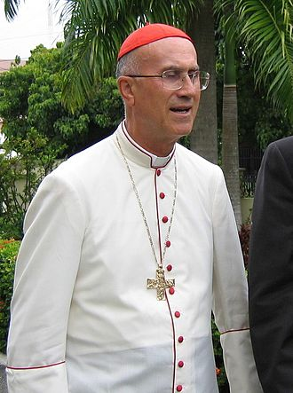 Cassock - Cardinal Tarcisio Bertone wearing a tropical white cassock trimmed in cardinalatial scarlet in Santo Domingo, Dominican Republic.