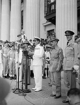 A man in a white uniform stands in front of a microphone on the steps of a building, surrounded by men in an array of uniforms.