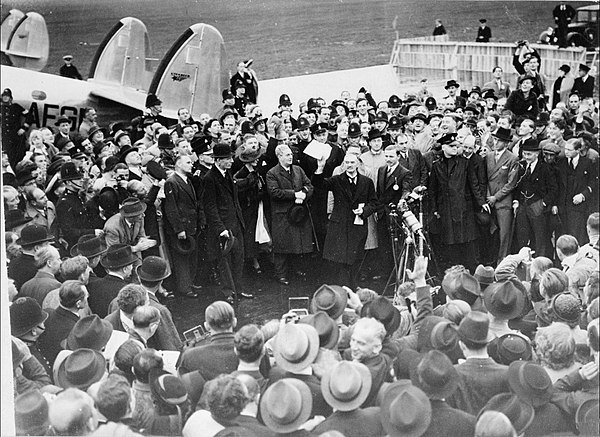 "After the summit, the British Prime Minister Neville Chamberlain returned to home where he declared that the Munich agreement meant ""peace for our time"" MunichAgreement.jpg"