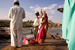 A Muslim couple being wed in India, as a Hindu man takes his ritual bath in the river.