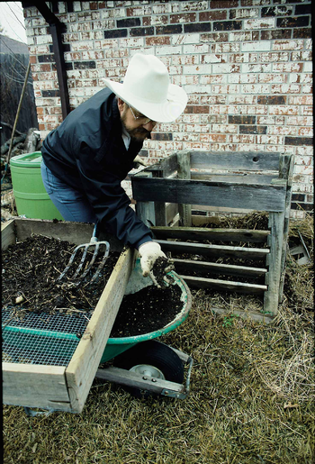 A homeowner sifts soil made from his compost b...