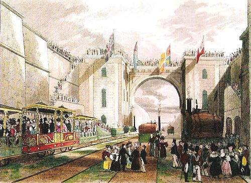 A large crowd standing in a deep railway cutting. On the railway tracks are three elaborately decorated carriages and a number of small locomotives.