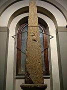 Photographie d'une stèle/obélisque en pierre assez imposante, exposé devant une fenêtre, avec un bas-relief en très mauvais état au milieu.