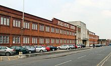 Image of a red brick building with a central front door, the words Rolls-Royce Limited appear above the door in white letters