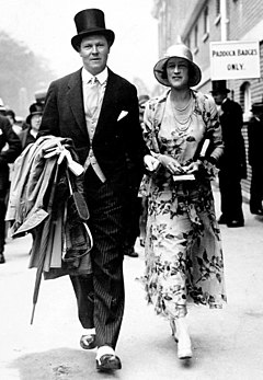 A man in a top hat and suit and a woman in a hat and dress walk towards the camera