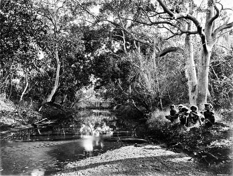 Black and white photograph of a creek - a shallow stream in a wooded area - with a small group of people squatting on the right-hand bank.