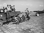 Pilots of No. 19 Squadron RAF stage a mock 'scramble' from the back of a truck at Fowlmere near Duxford, September 1940. CH1398.jpg