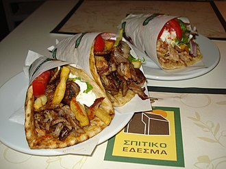 Gyro (food) - Gyros sandwiches/wraps in Greece, with meat, onions, tomato, lettuce, fries, and tzatziki rolled in a pita