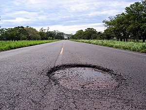 A large pothole on a country road.