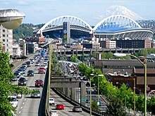 An elevated highway with inbound traffic seen atop a double-decked structure. Several buildings can be seen off to the side of the highway, while CenturyLink Field and Mount Rainier can be seen in the background.