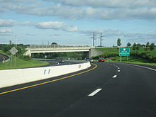 Ground-level view of a divided freeway at a curve in the road; a green exit sign and a white bridge are visible in the distance.