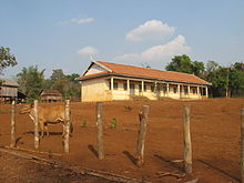 Small white building standing in a field of red earth. A cow wanders in the foreground.