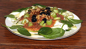 "A raw tomato ""sauce"" with olives, celery, spinach and walnuts on courgette ""pasta noodles""."