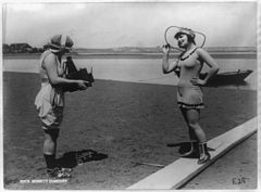 Roxy McGowan and Mary Thurman in bathing suits, with one taking the other's picture on beach, posed for Mack Sennett Productions (3b43826).jpg