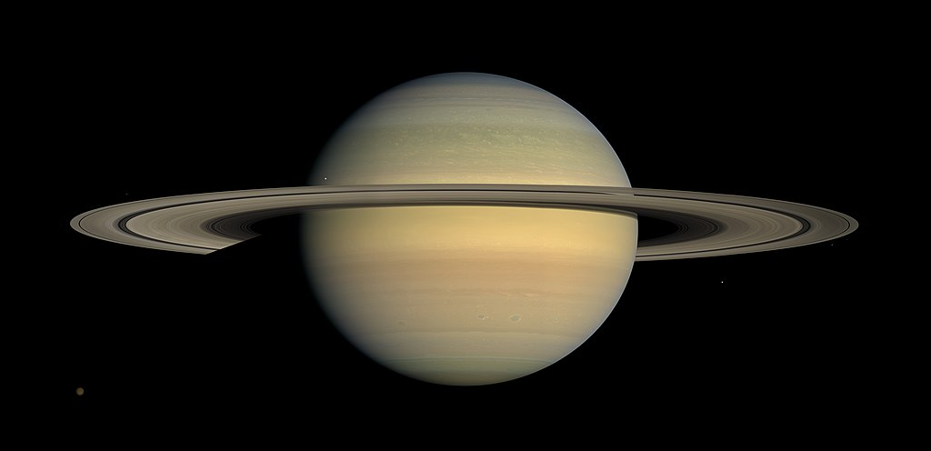 Saturnus dicitrakan dalam warna alami mendekati titik balik, difoto oleh Cassini pada Juli 2008. Titik di sudut kiri bawah adalah Titan