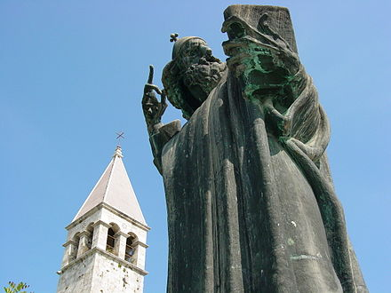 Grgur Ninski statue by Ivan Mestrovic, with a tower of the Diocletian's Palace in the background Sculpture of Gregorious of Nin - Split - Croatia.jpg